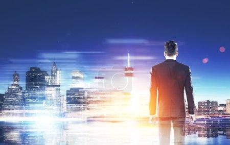 Foto de Hombre de traje de pie con la espalda al espectador y mirando el panorama de la gran ciudad. Concepto de empresas comerciales y de negocios internacionales. Imagen tonificada - Imagen libre de derechos