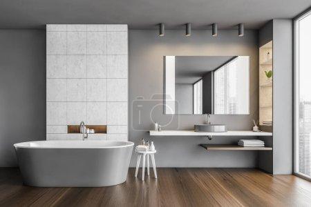 Dark bathroom with bathtub and mirror with sink ne...