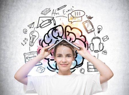 Photo pour Jolie femme étudiante intelligente en t-shirt blanc décontracté tenant livre ouvert sur la tête comme la maison. Éducation commerciale colorée et croquis e-learning dessinés sur le mur derrière - image libre de droit