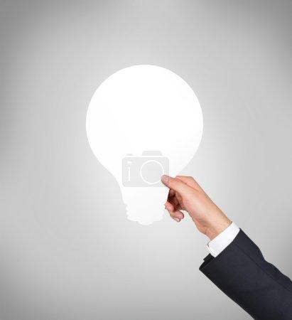 Photo pour Main tenant ampoule en papier sur fond gris - image libre de droit