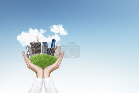 Photo for Hands holding city on green grass hill - Royalty Free Image
