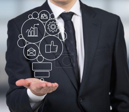 Photo pour Homme d'affaires tenant icône d'affaires dans la lampe de forme - image libre de droit