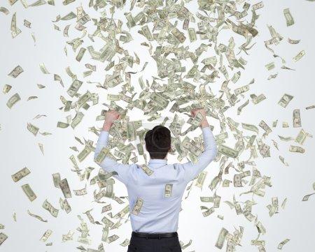 businessman catching falling dollar