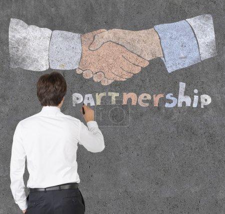 businessman drawing partnership symbol