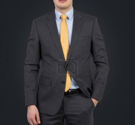 Photo pour Homme d'affaires en costume et cravate jaune sur fond noir - image libre de droit