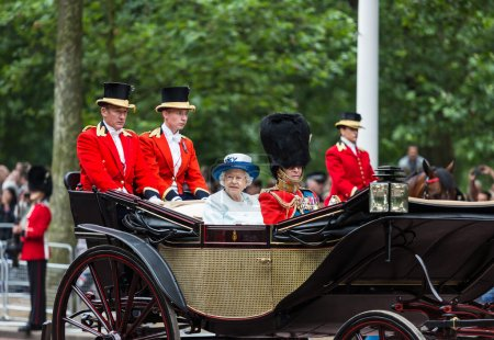 Foto de LONDON - JUNE 14: Queen Elizabeth II and Prince Philip seat on the Royal Coach at Queen's Birthday Parade, also known as Trooping the Colour, on June 14, 2014 in London, England. - Imagen libre de derechos