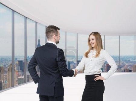 at the business meeting. Handshake as a concept of successful deal. New York panoramic office background.