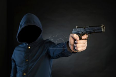 Photo for Armed person in a hoodie is pointing a handgun at the target. - Royalty Free Image