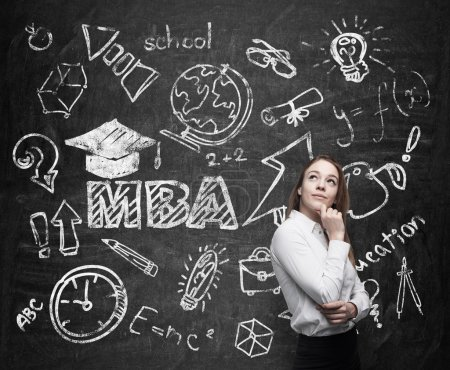 A lady is pondering over the business degree. A concept of the MBA degree. Drawn educational icons on the chalkboard.