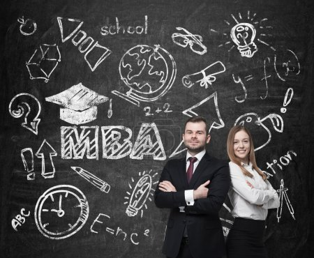 Young students are pondering over the business degree. A concept of the MBA degree. Drawn educational icons on the chalkboard.