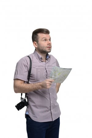 Photo for Handsome tourist with camera is thinking about visit points. Isolated. - Royalty Free Image
