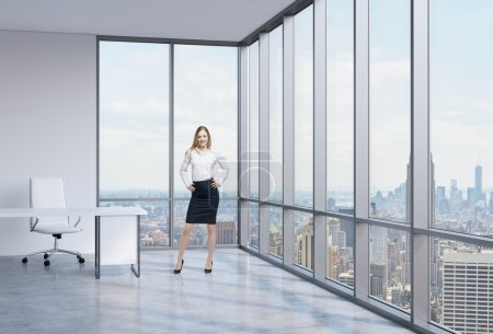 Beautiful smiling employee is standing in the office with New York panoramic view. A concept of the modern workplace.