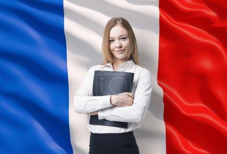 Foto de Señora de negocios sonriente en una camisa blanca con una carpeta negra. Bandera francesa como fondo. - Imagen libre de derechos