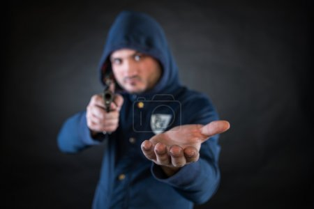 A person in a hoodie is aiming and holding the other hand. A concept of the robbery.