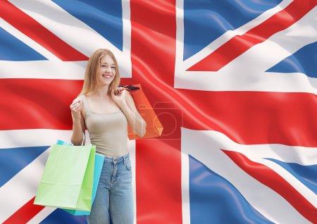 Photo pour Une jeune femme heureuse avec les sacs colorés des boutiques chics. Grande-Bretagne fond de drapeau. - image libre de droit