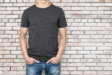 Man wearing dark grey t-shirt, brick wallbackground. Hands in the pockets.