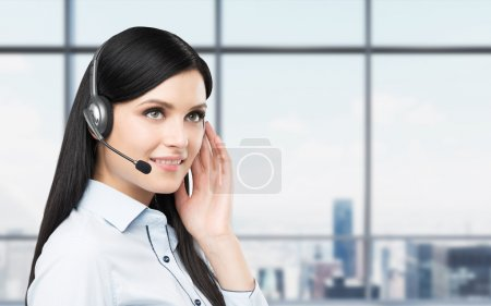 Portrait of smiling cheerful support phone operator in headset. New York panoramic office background.