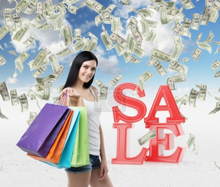 Beautiful smiling brunette woman with the colourful shopping bags from the fancy shops. Falling dollar notes from the cloudy sky. A concept of discounts and sales.