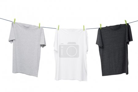 Close up of three t-shirts on the rope (grey, white and dark grey). Isolated.