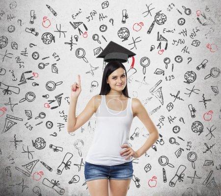 Photo pour Brunette dame est présente une nécessité de l'enseignement supérieur. Chapeau de fin d'études au-dessus de sa tête. Des icônes éducatives sont dessinées sur le fond concret . - image libre de droit