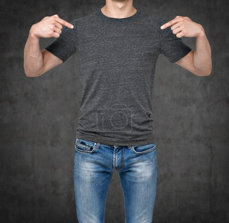 Close-up of a man pointing his fingers on a blank grey t-shirt. Dark concrete background.