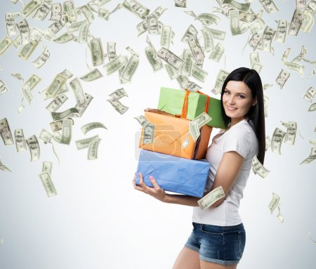A brunette woman is holding three colourful gift boxes. Falling dollar notes from the ceiling.