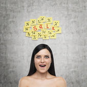 Portrait of an astonished brunette girl. Yellow stickers with the word ' sale ' are hanged on the concrete wall.