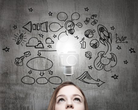 Young business lady is looking for new business ideas. Drawn business icons on the concrete wall and a light bulb as a concept of new idea.