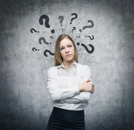A portrait of a beautiful lady with questioning expression and question marks above her head. Concrete background.