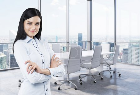 Beautiful brunette in a corner conference room. Modern office with huge windows and amazing New York panoramic view.
