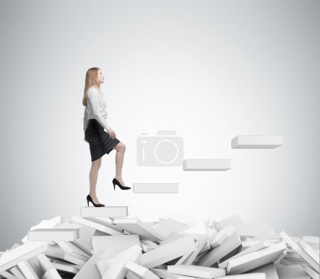 Young business woman is going up to the stairs. A concept of education process. White books on the floor.