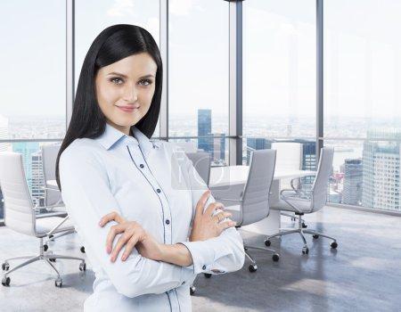 Photo pour Belle brune dans une salle de conférence du coin. Bureau moderne avec d'immenses fenêtres et vue panoramique sur New York. - image libre de droit