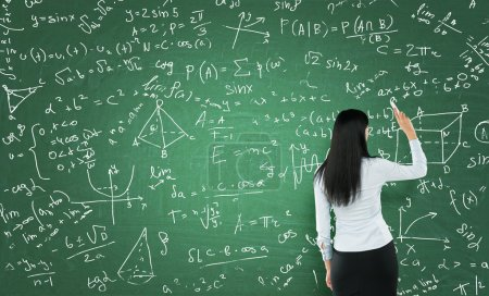 Rear view of a thoughtful woman who is writing math calculations on green chalk board.