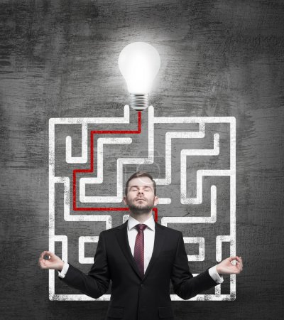Meditative businessman and solved labyrinth with a light bulb on the black chalk board.