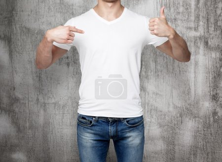 Close-up of a man pointing his finger to a blank t-shirt, and the thumb up. Concrete background.