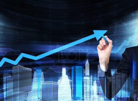 Photo pour Une main dessine une flèche croissante sur l'écran de verre. Un concept de services financiers aux entreprises. Hologramme du paysage urbain . - image libre de droit