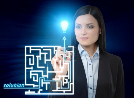 Brunette business woman is drawing a labyrinth with solution on the glass screen. Modern hologram illusion.