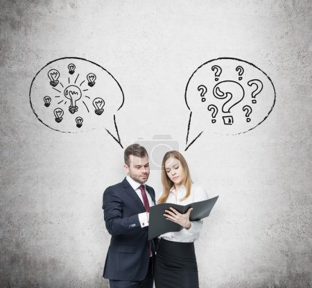 Business couple are arguing about business project . A couple in formal clothes are holding a black document folder. Light bulbs and question marks are drawn on the wall behind them. Concrete backgrou