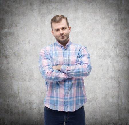 Photo pour Jeune homme beau en chemise décontractée avec les mains croisées. Mur en béton . - image libre de droit