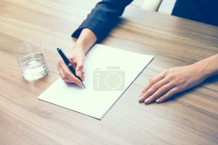 Closeup of a business woman's hands while writing down some essential information. A glass of water, paper and a pen. A concept of drafting the contract. Toning filter.