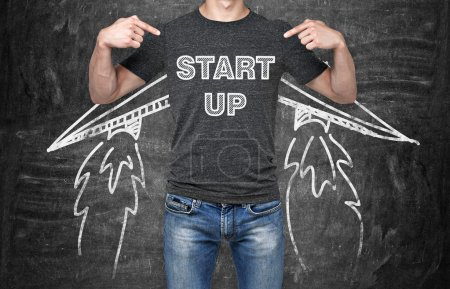 Photo for A businessman is pointing out in the chest where is a word collocation ' start up '. A concept of the starting up new business. Drawn wings. Black chalk board on the background. - Royalty Free Image