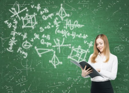 Young lady is holding a black document folder and a range of math formulas are drawn on the green chalkboard.