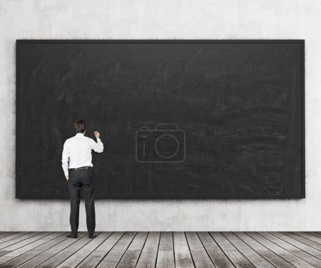 Rear view of the man who is going to write something on the black chalkboard. Wooden floor and concrete wall. A concept of the beginning of new academic year. A class room.