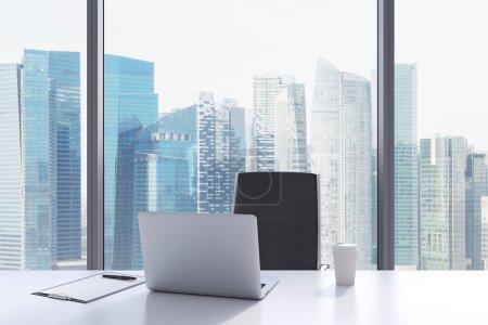 Photo pour Un lieu de travail dans un bureau panoramique moderne avec vue sur Singapour. Une table blanche, fauteuil en cuir noir. Ordinateur portable, bloc-notes pour notes et un chapeau de café sont sur la table. intérieur Office. rendu 3d. - image libre de droit