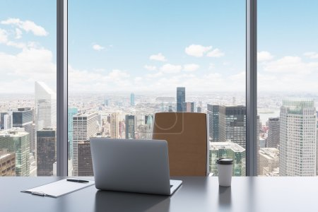 Photo pour Un lieu de travail dans un bureau panoramique moderne avec vue sur New York. Une table gris, fauteuil en cuir brun. Ordinateur portable, bloc-notes pour notes et un chapeau de café sont sur la table. intérieur Office. rendu 3d - image libre de droit