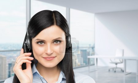 Front view of the smiling brunette support phone operator with headset. Panoramic office workplace on the background. New York city view.