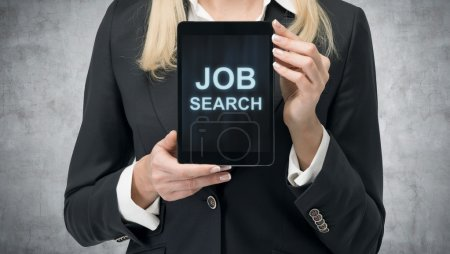 Blonde woman in formal suit presents a tablet with the words 'Job Search' on the screen. A concept of recruitment process. Internship and graduate programmes. Concrete background.