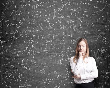 Beautiful lady in formal clothes thinking about possible solutions of the quantitative problems. Math formulas are drawn on the black chalkboard.