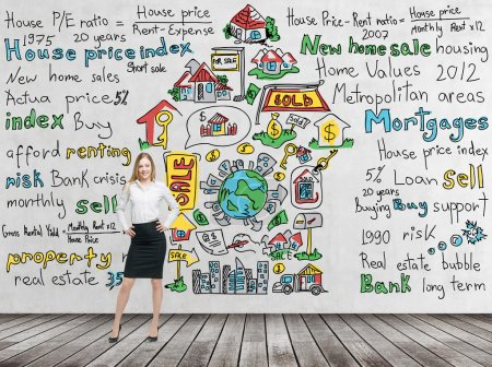 Full length beautiful woman in formal clothes with hands on the waist. Colourful ' home sales ' icons are drawn on the concrete wall. Risk analysis of the mortgage loan. Wooden floor.