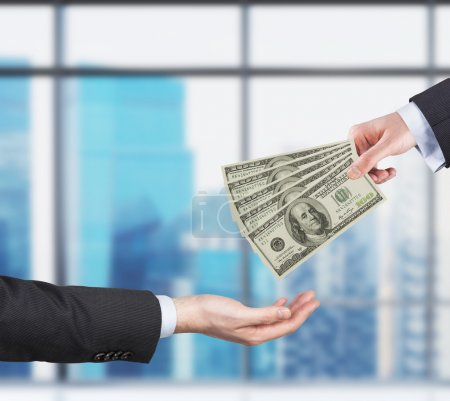 Two hands, money transferring process. Dollar bills. Business city view on the background form the panoramic windows of the modern office.